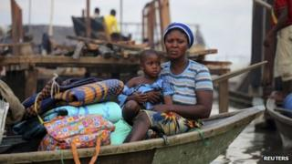 A woman sits in a canoe with her belongings as the metropolitan government begins the demolition of structures in the Makoko riverine community in Lagos July 16, 2012.