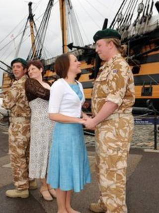 Cast members from Much Ado About Nothing with HMS Victory in the background