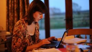 Generic image of a woman using a laptop at home