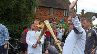 """Torchbearers stage the """"torch kiss"""" as the flame is handed over"""