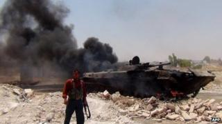 Image posted online purportedly showing rebel fighter standing next to a burning Syrian army armoured fighting vehicle in Jarjanaz, Idlib province (28 June 2012)