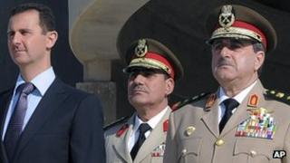 Syrian President Bashar Assad, left, stands with Syrian Defence Minister Dawoud Rajha, right, and an unidentified man during a ceremony in Damascus, Syria