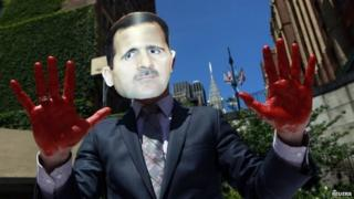 A protester from the activist organization Avaaz wearing a mask of Syrian President Bashar al-Assad