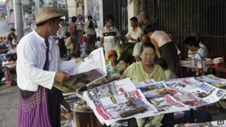 A man buys a weekly news journal at a roadside newspaper stand in Rangoon, Burma, 10 June, 2012