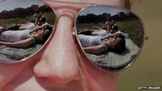 sunbathers reflected in sunglasses
