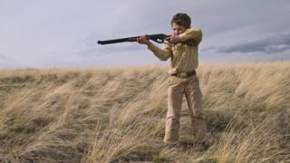 A young boy in a field aims a rifle