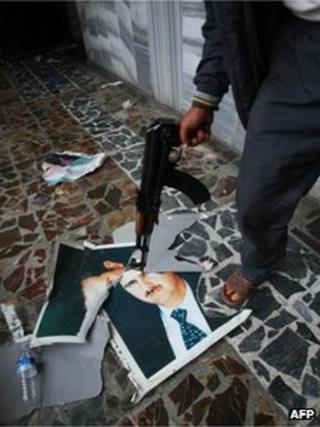 FSA fighter near Turkish border holding gun to picture of President Assad (22 July)