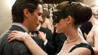 A publicity photograph from The Dark Knight Rises. Christian Bale as Bruce Wayne dances at a ball with Anne Hathaway (Catwoman). She is wearing a mask over her eyes.