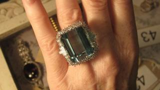 A trap-cut aquamarine and cluster ring with surround of brilliant and baguette – cut diamonds, in all white 18 ct gold