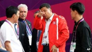 North Korean Women's football team staff member talks to officials at Hampden Park