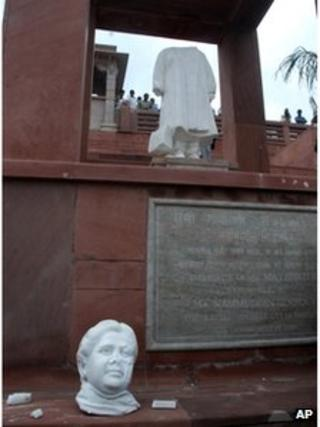 People look at the scene after a marble statue of former Uttar Pradesh Chief Minister Mayawati was vandalized by unidentified men at the Ambedkar Park in Lucknow, India, Thursday, July 26, 2012
