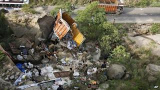Police officers inspect the wreckage at an accident site about 65 kilometers from Jammu, India, Friday, July 27, 2012.