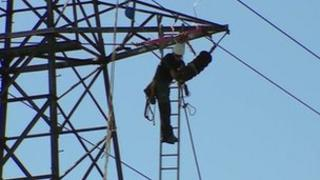 Power firm worker fixes cable