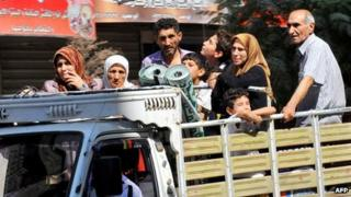 People leave the Aleppo city centre after shelling by Syrian government forces on 26 July