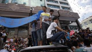 Local residents stand on smashed cars as they occupy the local government building during a protest against an industrial waste pipeline under construction in Qidong