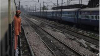 An Indian passenger looks out from the compartment of a stationary train following the power outage that struck in the early hours of Monday, July 30, 2012 at a train station in New Delhi, India