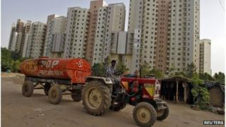 A water tanker moves past Malibu Towne residential apartments at Gurgaon, on the outskirts of New Delhi, June 16, 2012.