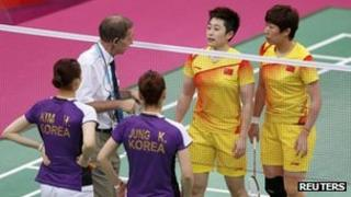 Tournament referee Torsten Berg (2nd L) speaks to players from China (in yellow) and South Korea during their women's doubles group play stage in London on 31 July 2012