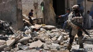 An Iraqi soldier stands guard at the site of a bomb attack in a market in the eastern Iraqi town of Zubaidiya (3 July, 2012)