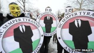 Members of Anonymous display the group's logo