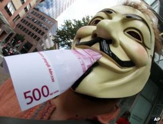 An activist of the occupy movement poses with a fake euro banknote in Frankfurt, home of the European Central Bank, 2 August
