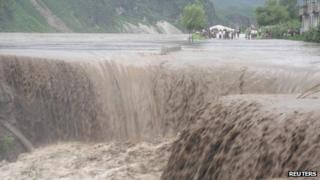 A handout photo from the Red Cross dated 24 July, 2012 shows North Korean residents standing next to a road as flood water pours into a caved-in area in Songchon county, South Pyongan Province
