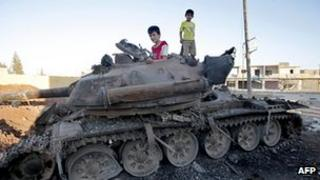 Children play on an abandoned tank close to the city of Aleppo