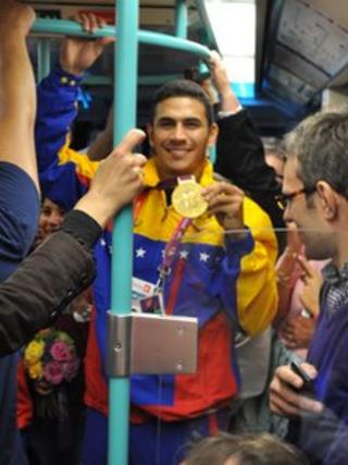 Ruben Limardo shows off gold medal on the DLR, 2 August 2012, pic courtesy of Chris Scanlan