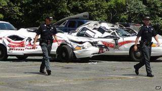 Sheriff officers walk past crushed cruisers at the Orleans County Sheriff's Department in Newport, Vermont on 2 August 2012