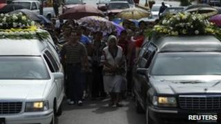 People walk in a funeral cortege in Muzquiz, Mexico