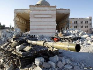 A boy plays on a tank near a ruined mosque in Azaz, 47km (29 miles) north of Aleppo, 3 August