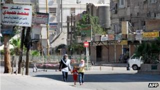 Girls walk down the street in the deserted neighbourhood of Sayyida Zeinab on the southern outskirts of the the Syrian capital, Damascus, on 29 July