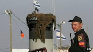 A picture taken on March 19, 2007 shows an Egyptian border policeman standing guard not far from an Israeli watch tower at the Karm Abu Salem border gate