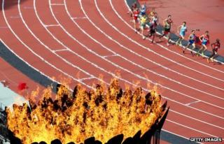 Athletes in steeplechase heats run pas the Olympics cauldron