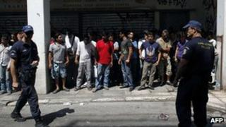 Police detain a group of immigrants in central Athens on August 5, 2012