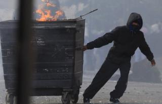 A masked youth pulls a burning bin in Hackney, east London, during the August riots