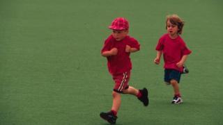Two children running across school field