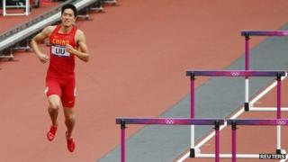 China's Liu Xiang hops down the track after crashing into the first hurdle and failing to finish his men's 110m hurdles heat at the London 2012 Olympic Games at the Olympic Stadium 7 August, 2012