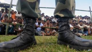 An Indian defence serviceman keeps watch as displaced Muslim villagers look on in the background at a relief camp in Butgaon village in Assam state's Kokrajhar district on July 28, 2012.