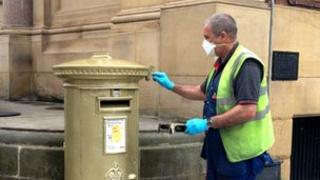 A Royal Mail employee applied a new layer of gold paint to the postbox