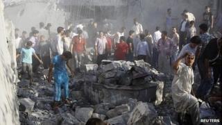 Men search rubble in Tal Rifaat, near Aleppo