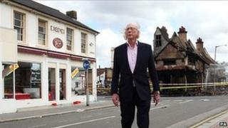 Maurice Reeves stands near the destroyed shop and the smaller premises