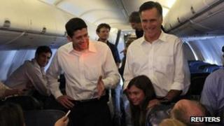 Republican US presidential candidate Mitt Romney (R) stands with his vice-president selection Congressman Paul Ryan and granddaughter Chloe while speaking to the media aboard a charter flight to Charlotte, North Carolina from Chantilly in Virginia on Saturday