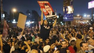 Supporters of Egypt's President Mohammed Morsi chant as they carry posters of him in front of the presidential palace in Cairo on Sunday