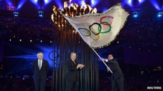 Rio de Janeiro Mayor Eduardo Paes waves the Olympic flag as IOC President Jacques Rogge applauds and London Mayor Boris Johnson watches