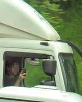 A motorist taking a picture on a mobile phone