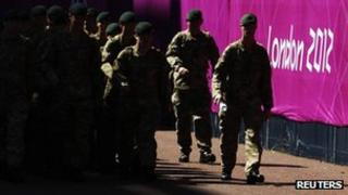 Soldiers patrol past signage for the London 2012 Olympic Games near the beach volleyball courts at Horse Guards Parade in London