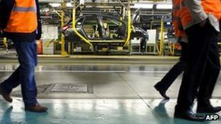 Visitors pass Peugeot production line