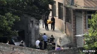 Police carrying away the body of Zhou Kehua in Chongqing