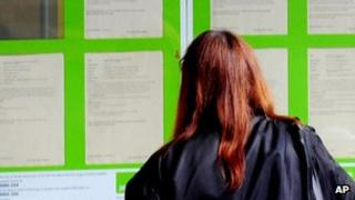 A woman looking into the window of a Job Centre